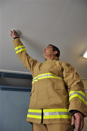 © The Looker Fireman testing a smoke detector